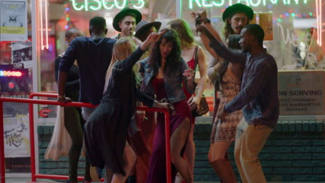 diverse group of hipster friends dance the night away on downtown austin street corner as cars pass in foreground. - generazione y video stock e b–roll