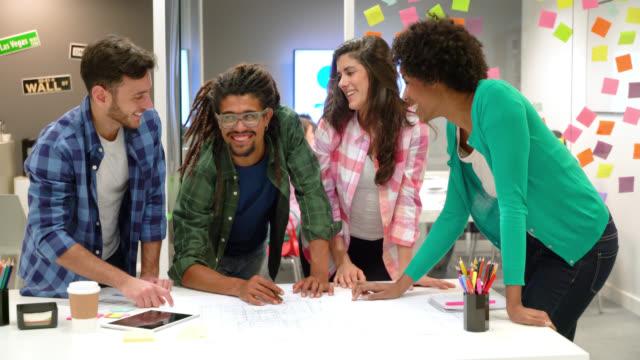 Un groupe diversifié de designers d'intérieur en regardant un plan remue-méninges des idées pour un l'espace