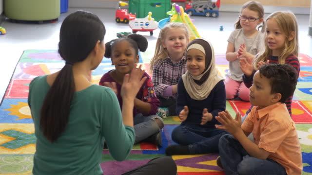 vídeos de stock, filmes e b-roll de grupo diversificado de crianças batendo palmas. - hijab