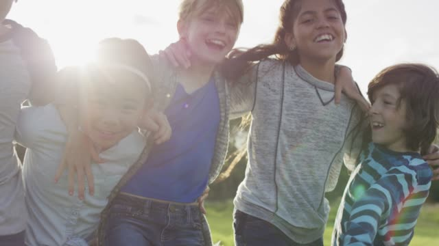 vidéos et rushes de groupe diversifié de jeunes embrassant à l'extérieur - public