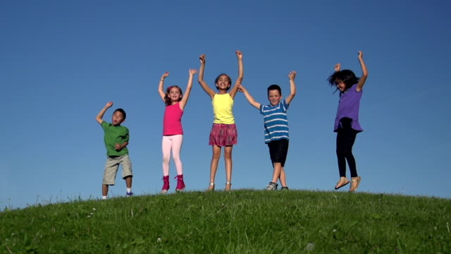 Diverse group of kids jumping on hill in slow motion