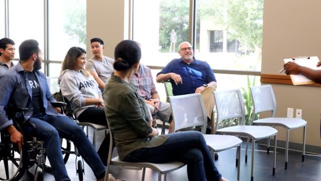 vídeos de stock, filmes e b-roll de o grupo diverso de veteranos masculinos e fêmeas recolhe para uma reunião do grupo de apoio - orientação