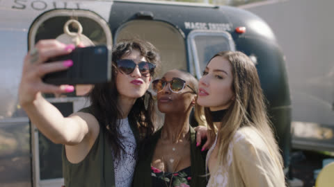 a diverse group of millennial hipster women take a selfie in front of a boho clothing mobile fashion truck - generation z点の映像素材/bロール