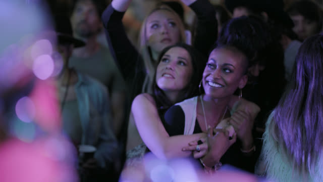diverse group of millennial hipsters hug and dance in the front row of a popular music festival - beatnik stock videos & royalty-free footage