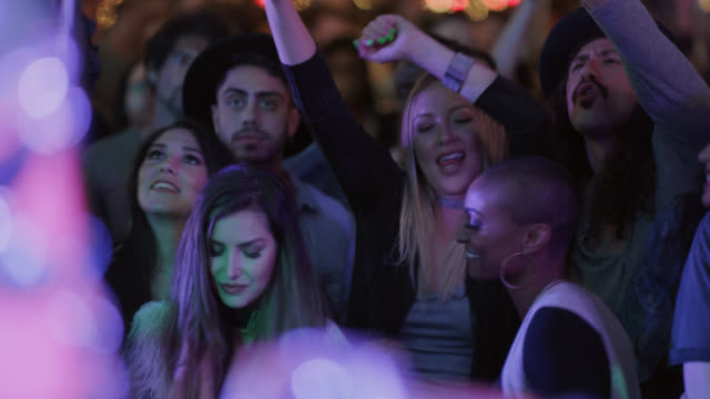 diverse group of millennial hipsters rock out in the front row of a popular music festival - beatnik stock videos & royalty-free footage