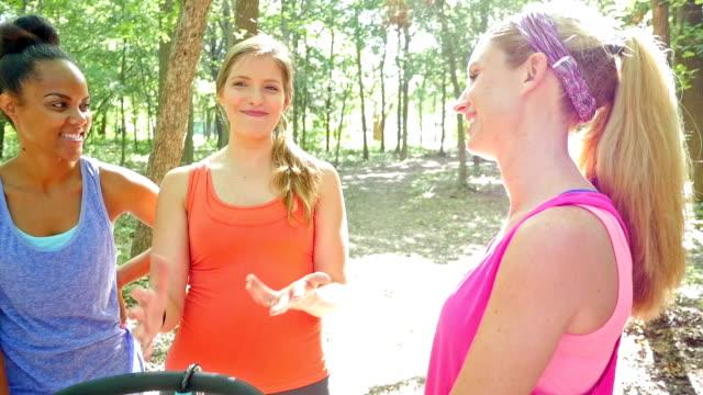 多様なグループの女性に話すのは、エクササイズ中一緒に公園 - 噂点の映像素材/bロール
