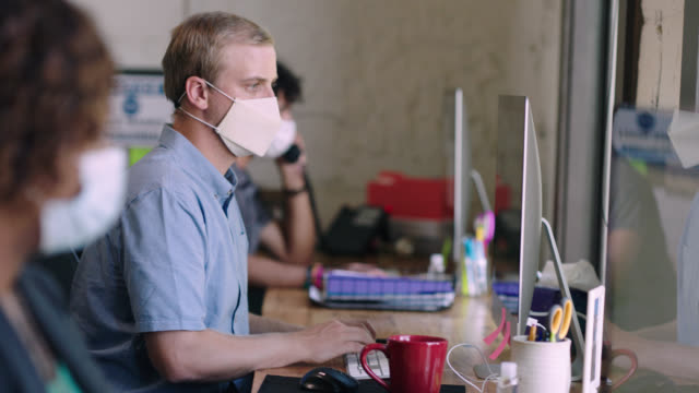 diverse group of office workers wear face masks and sit six feet apart at workstations - 20 29 years stock videos & royalty-free footage