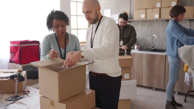 vídeos de stock e filmes b-roll de diverse group of people arranging customers orders for drop shipping - crachá etiqueta
