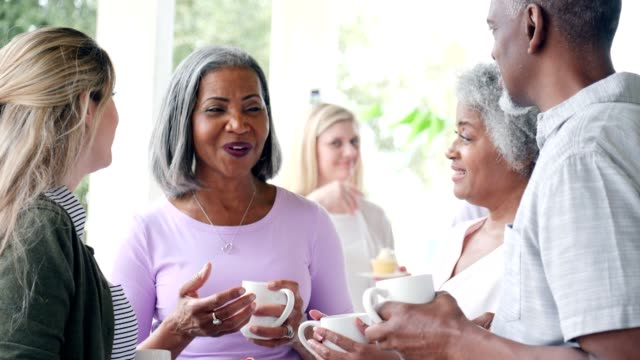 Diverse group of people attend charity bake sale