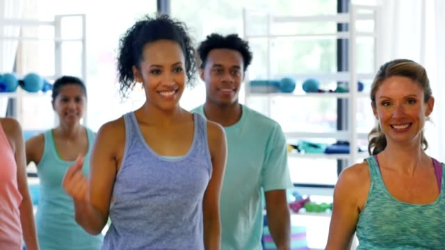 Diverse group of people dance in unison during aerobics class