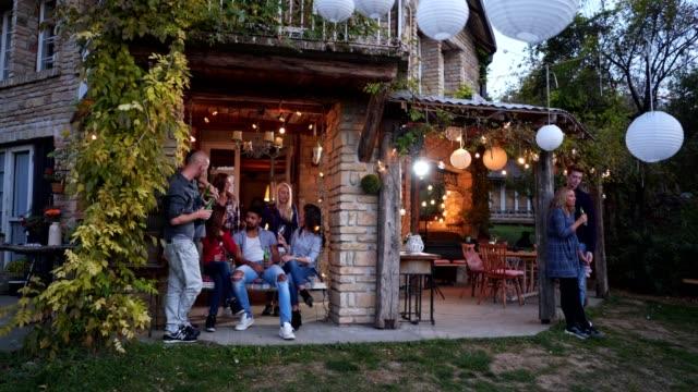 家のポーチでドリンクを楽しむ人々の多様なグループ - large group of people点の映像素材/bロール