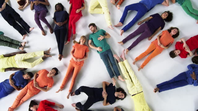 diverse group of people lie down on white studio floor - hands behind head stock videos and b-roll footage