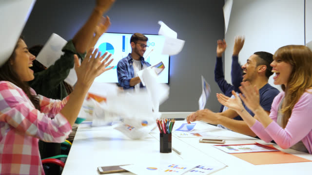 diverse group of salespeople at a meeting and manager very happy because of their sales so all celebrate throwing the documents to the air - throwing stock videos and b-roll footage