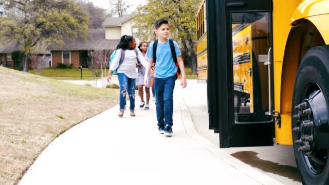 stockvideo's en b-roll-footage met diverse groep schoolkinderen die schoolbus instappen - bus