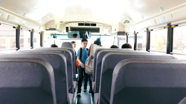 diverse group of schoolchildren boarding school bus - bus stock videos & royalty-free footage