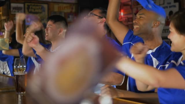 diverse group of sports fans cheering at the bar - home run stock videos & royalty-free footage