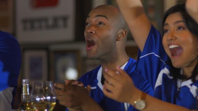 vídeos y material grabado en eventos de stock de grupo diverso de aficionados del deporte que animan en el bar - barra futbol