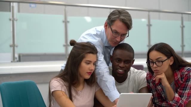 diverse group of students and teacher looking at something on tablet during class - post secondary education stock videos & royalty-free footage