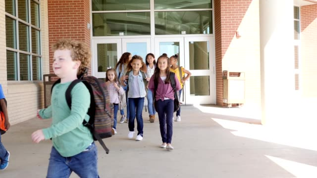 diverse group of students leave school at the end of the day - elementary student stock videos & royalty-free footage