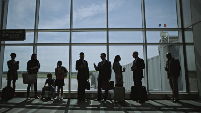 slo mo. diverse group of travelers assembled in front of airport terminal window. - internationale geschäftswelt stock-videos und b-roll-filmmaterial