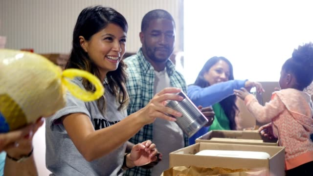 diverse group of volunteers pack food donations during the holidays - gruppo multietnico video stock e b–roll