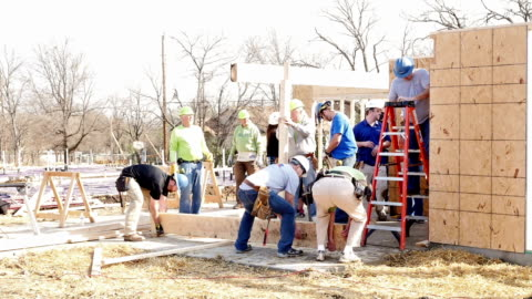 diverse group of volunteers raise beam on home for charity - volunteer stock videos & royalty-free footage