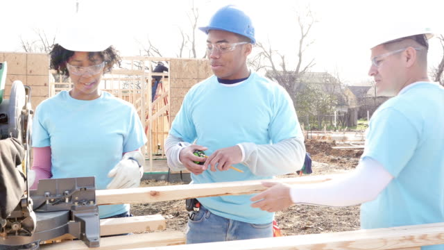 diverse group of volunteers work on home built for charity - mid adult men stock videos & royalty-free footage