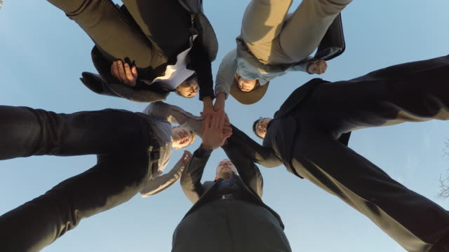 vidéos et rushes de diverse group of young friends bonding hands together cheerful raising arms in the air showing team spirit - cinq personnes