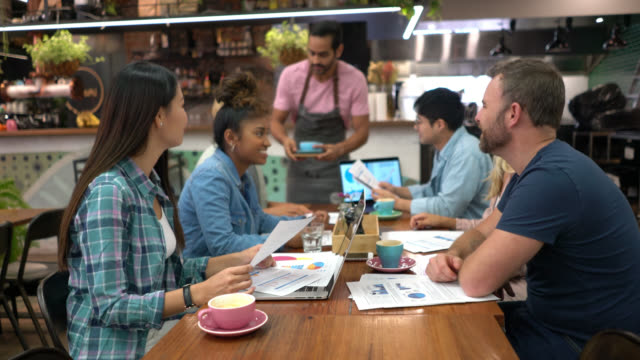 diverse group of young people at a meeting in a restaurant looking at documents and talking while waiter is serving coffee - waiter stock videos & royalty-free footage