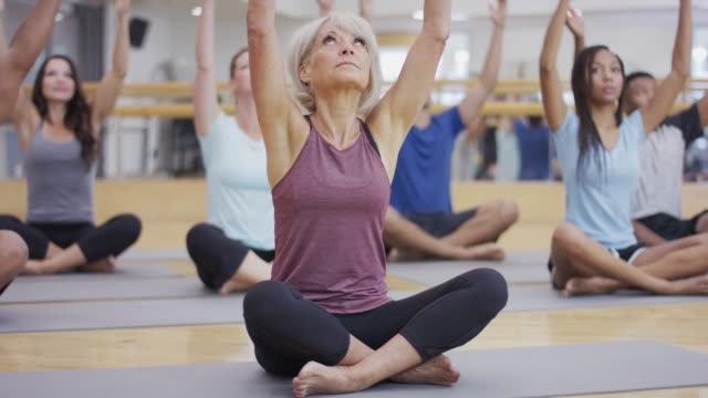 diverse group yoga class - terza età video stock e b–roll