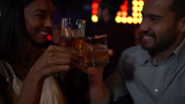 ウイスキーの笑顔と楽しみで乾杯バーで多様な幸せなカップル - スナック点の映像素材/bロール