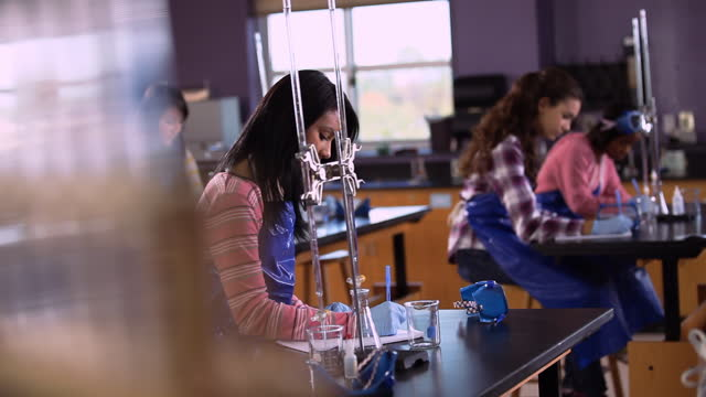 diverse high school students take notes in a science lab classroom. - secondary school child stock videos & royalty-free footage