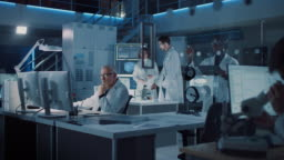 Diverse International Team of Industrial Scientists and Engineers Wearing White Coats Working on Heavy Machinery Design in Research Laboratory. Professionals Using Computers and Talking