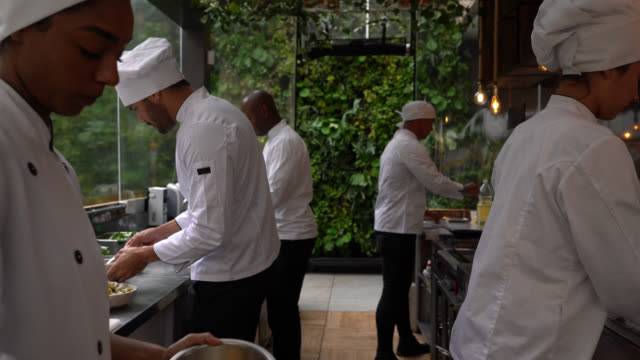 diverse kitchen staff preparing orders of breakfast at the restaurant looking busy - kitchen stock videos & royalty-free footage