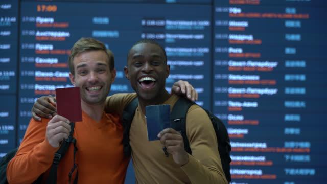 diverse männliche freunde am flughafen stehen vor der ankunftspfafel, die den reisepass zeigt, während sie vor der kamera glücklich sind - flugpassagier stock-videos und b-roll-filmmaterial