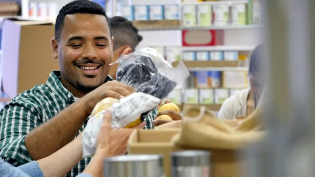 vídeos de stock e filmes b-roll de diverse male friends talk with one another while volunteering in food bank - organização sem fins lucrativos
