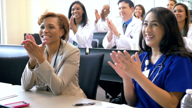 Diverse medical professionals applauding speaker at healthcare conference
