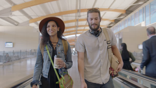 Diverse millennial couple talks, smiles as they walk down moving sidewalk in airport terminal.