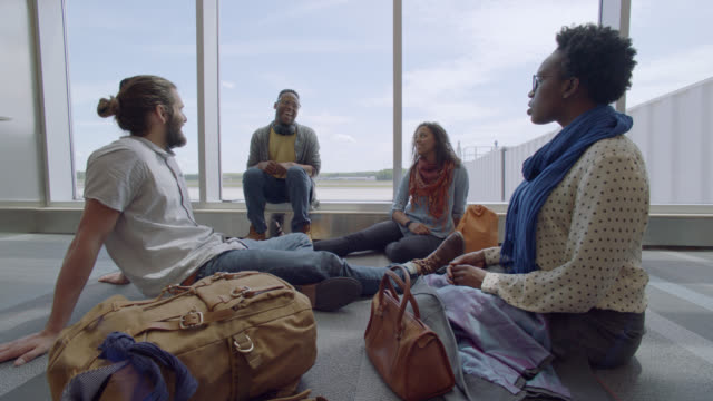 vidéos et rushes de diverse millennial travelers laugh and relax in a group at airport terminal gate. - mode of transport