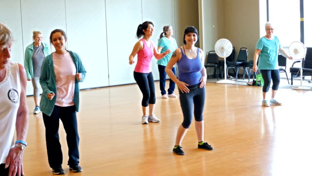 Diverse mixed age group of women doing dance aerobics in exercise class
