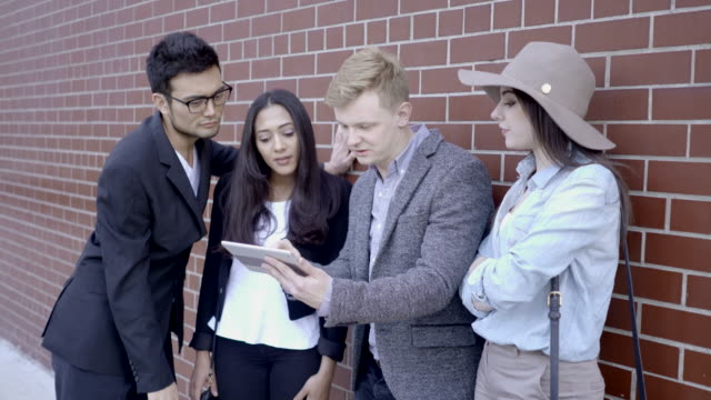 diverse multi ethnic group of young people talking together outdoors on city street - technophile stock videos & royalty-free footage