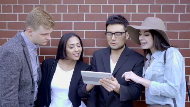 diverse multi ethnic group of young people talking together outdoors on city street - entusiasta di tecnologia video stock e b–roll
