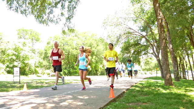 Diverse race competitors running past during marathon or 5k charity race