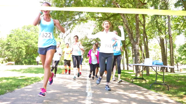Diverse runners crossing finish line during charity race