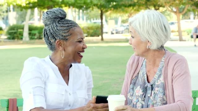 vídeos y material grabado en eventos de stock de chat de diversos senior femenino a un café en un parque de la ciudad - amistad femenina