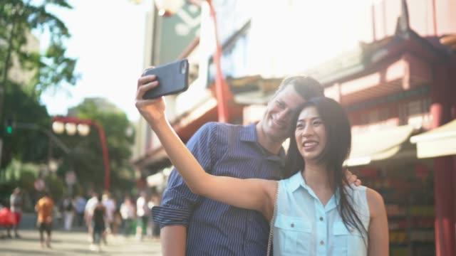 vídeos de stock, filmes e b-roll de pares de sorriso diversos que tomam um selfie na cidade - ponto turístico