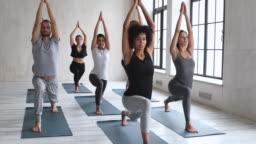 Diverse sportive people taking part at yoga session performing Virabhadrasana
