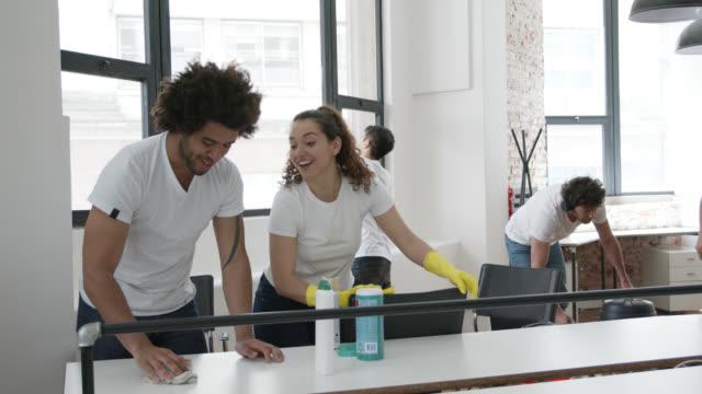 stockvideo's en b-roll-footage met divers team van schoonmakers doen een schoonmaakservice op een kantoor terwijl praten en glimlachen-serviceconcepten - dienstverlener