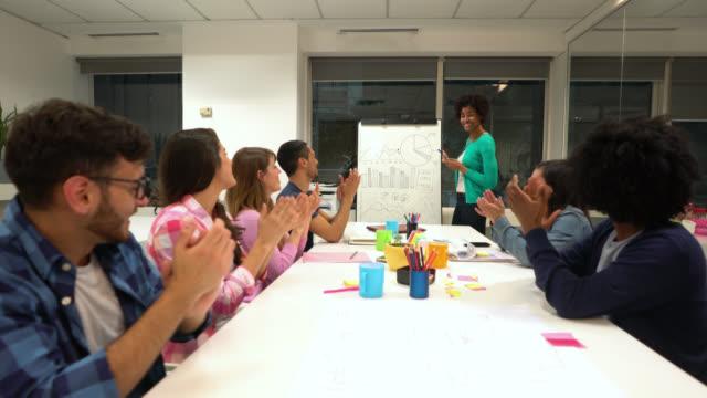 vídeos de stock, filmes e b-roll de equipe diversificada de criativos para uma reunião e preto mulher apontando para uma placa com gráficos falando e, em seguida, todos aplaudiram no final - gráfico