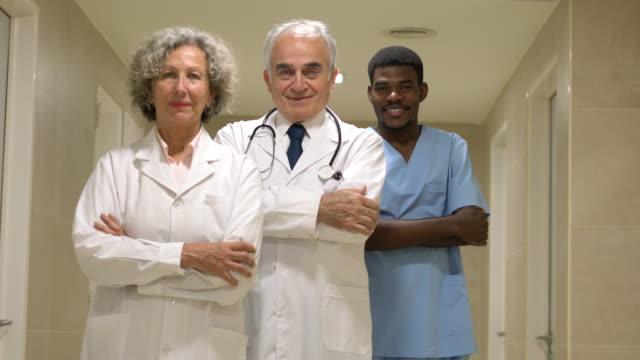 vídeos y material grabado en eventos de stock de diverso equipo de médicos y un cirujano negro en el hospital frente a la cámara sonriendo - bata de laboratorio